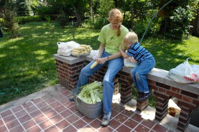 Photo: A woman readies corn for cooking with her young son as a distraction.