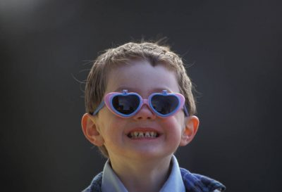 Photo: A young boy wearing heart glasses shows a wide smile.
