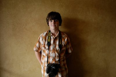 Photo: A teenage boy poses with his camera.