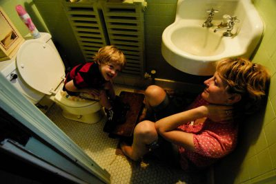 Photo: A mother potty-trains her 3-year-old son in the bathrooom of their home.