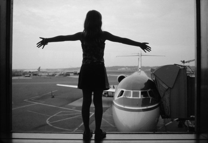 Photo: A girl looks out the airport window at the planes on the runway.
