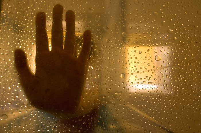 Photo: As seen through a damp shower door, a little girl is silhouetted by a window.