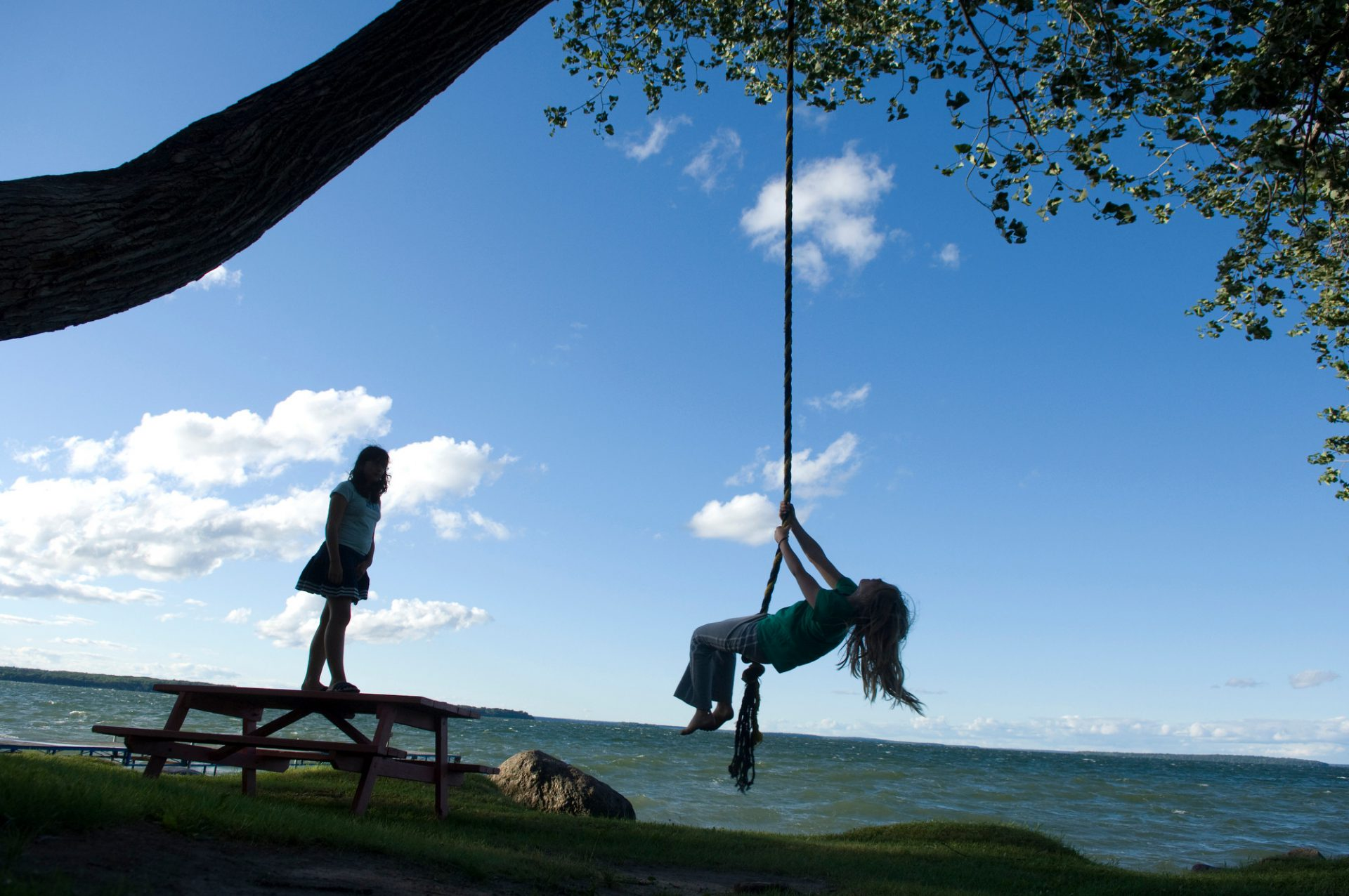 Photo: Two girls play on a rope swing along the shores of Leech Lake, Minnesota.