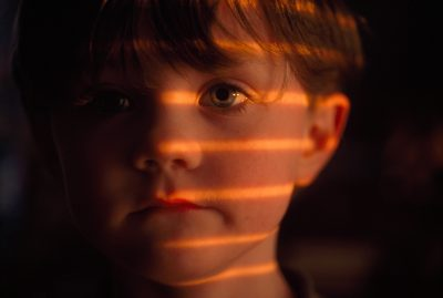 Photo: Portrait of a young boy with light seeping from blinds across his face.
