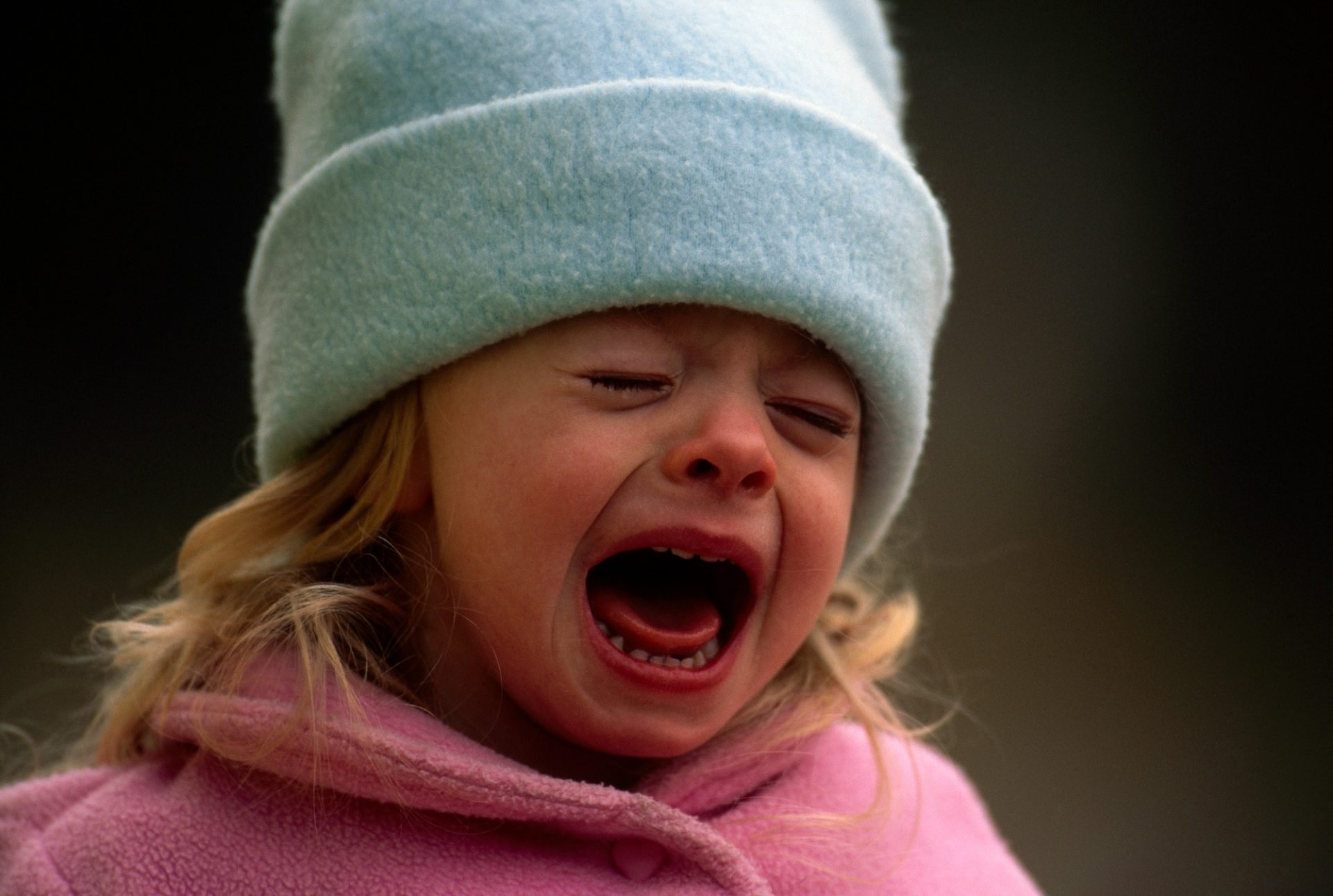 Photo: A young girl in winter clothing, crying.