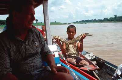 Photo: A local boy brings a caiman to tourists near Manaus, Brazilon the Amazon River.