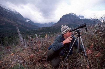 Photo: Doug Chadwick watches wildlife through a scope in Glacier National Park, MT.