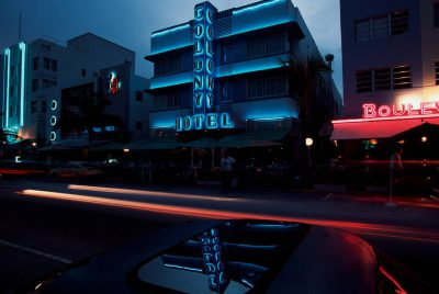 Photo: Cars whiz by art deco buildings in Miami's South Beach.