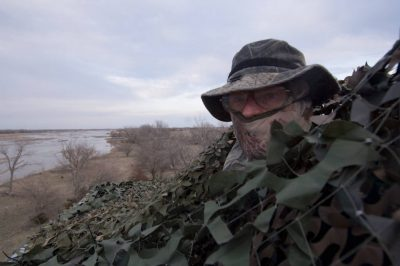 Photo: An ecologist is shown in camo looking out over the Sandhill Crane roost at Rowe Sanctuary near Gibbon, Nebraska.