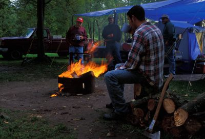 Photo: Men socialize around a campfire in rural Minnesota.