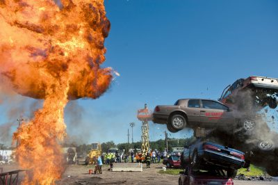 Photo: A stunt man performs a car jump from a flaming ramp at the Iowa state fair.