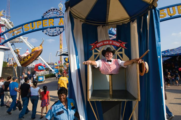Photo: A mirror illusion makes the midway barker appear like half a man at the Texas state fair.