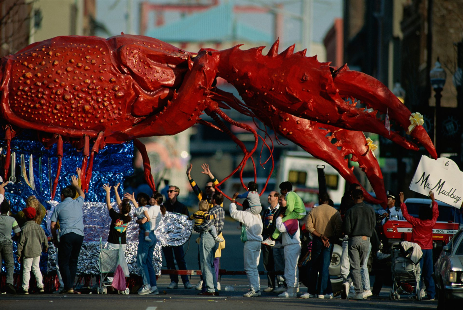 Photo: Louisianans revel beneath a giant crayfish Mardi Gras float.