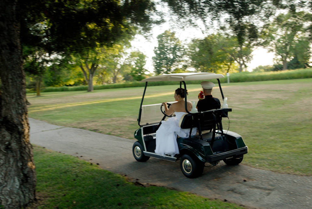 Photo: A bride and groom ride on a golf cart after their wedding.