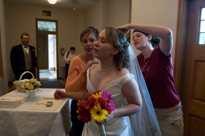 Photo: Two bridesmaids help a Nebraska bride get ready for her big day.