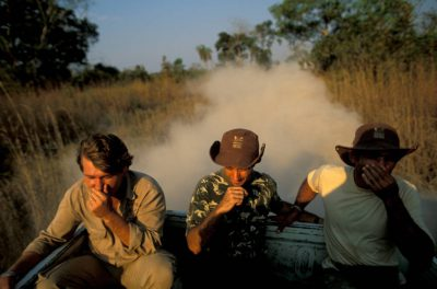 Photo: Three men try to shield their faces as clouds of dust billow up from a dirt road.