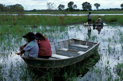 Photo: Two women wash clothes in the marsh while their children watch from a boat.