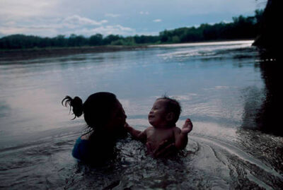 Photo: A native mother and her child bathe in the Tuichi River, a tributary of the Amazon, in Madidi National Park, Bolivia.