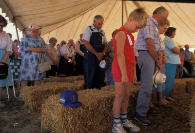 Photo: An 8-year-old boy prays at a Sunday morning service during the country threshing days in Goessel, Kansas.