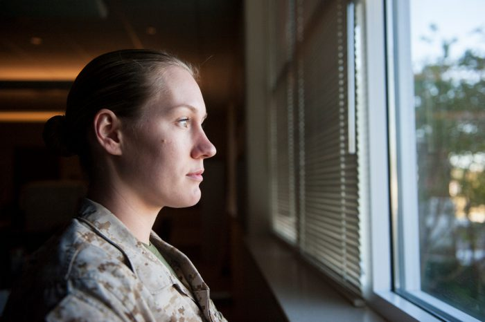 Photo: A military woman looks out of a window.
