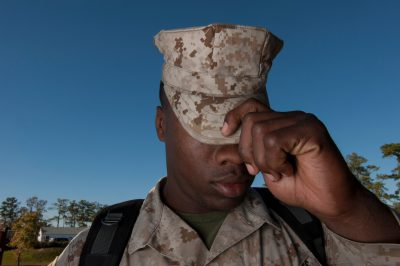 Photo: A military man adjusts his hat.