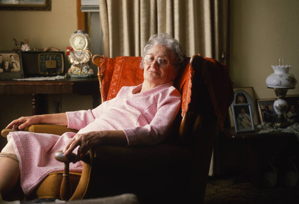 Photo: An elderly woman relaxes at home in her armchair.