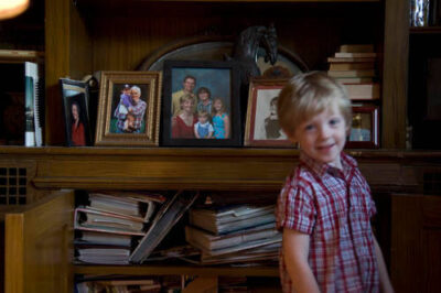 Photo: A young boy stands in front of his family's portraits at his home in Lincoln, Nebraska.