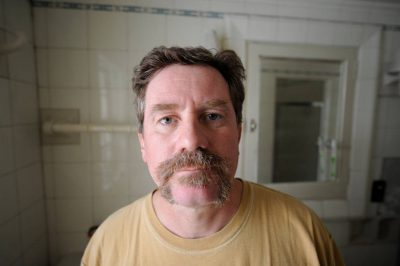 Photo: A man looks at his handlebar moustache in the mirror.