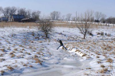 Photo: A man jumps over a snowy, frozen creek at the Sartore farm near Dunbar.