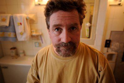 Photo: A man looks at his facial hair in the mirror.