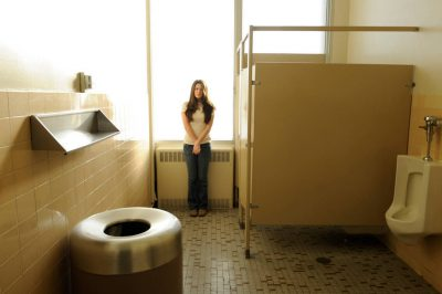 Photo: A young woman waits patiently to use the bathroom.