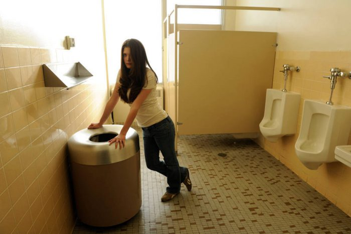 Photo: A young woman poses against a trash can in a restroom.