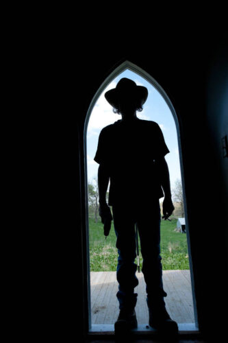 Photo: A silhouette of a man standing in the doorway of an old farmhouse in Dunbar, Nebraska.
