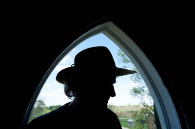 Photo: A silhouette of a man standing in a arched window in an old farmhouse in Dunbar, Nebraska.