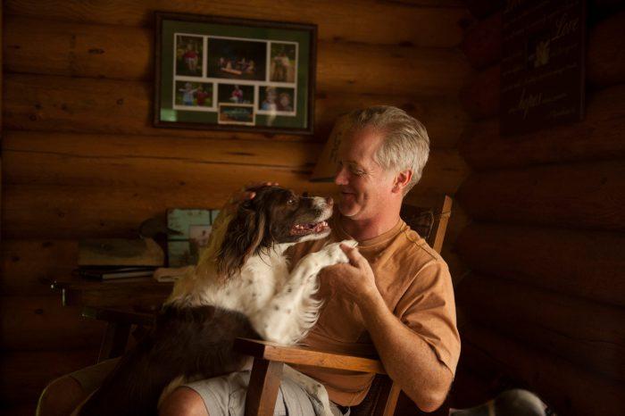 Photo: A man pets his English springer spaniel.