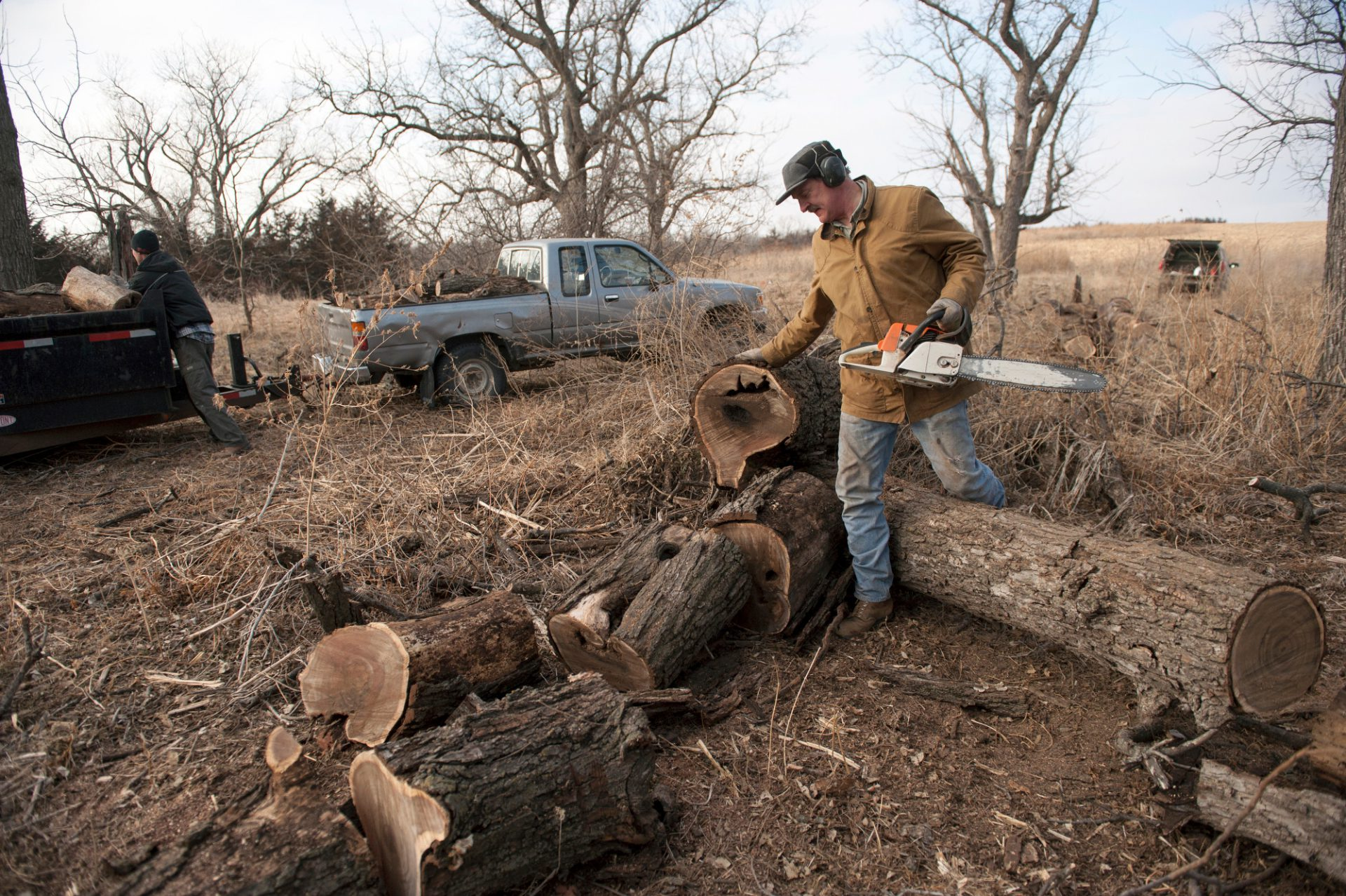 Photo: Two men cut logs in Ceresco, Nebraska.