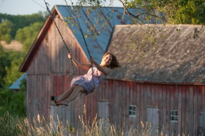 Photo: A teenage girl swings on a farm house near Dunbar, NE.
