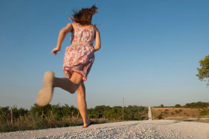 Photo: A teenage girl runs down a country road near Dunbar, NE.