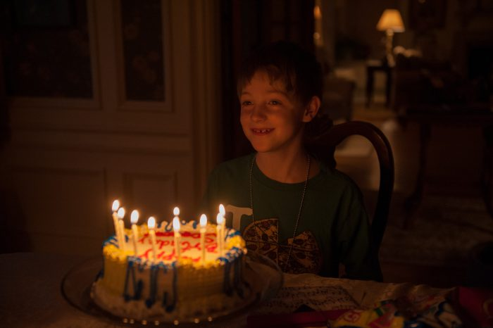 Photo: A young boy gets ready to blow out his birthday candles, Lincoln, Nebraska.