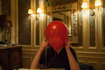 Photo: A teenage girl hides behind a birthday balloon, Lincoln, Nebraska.