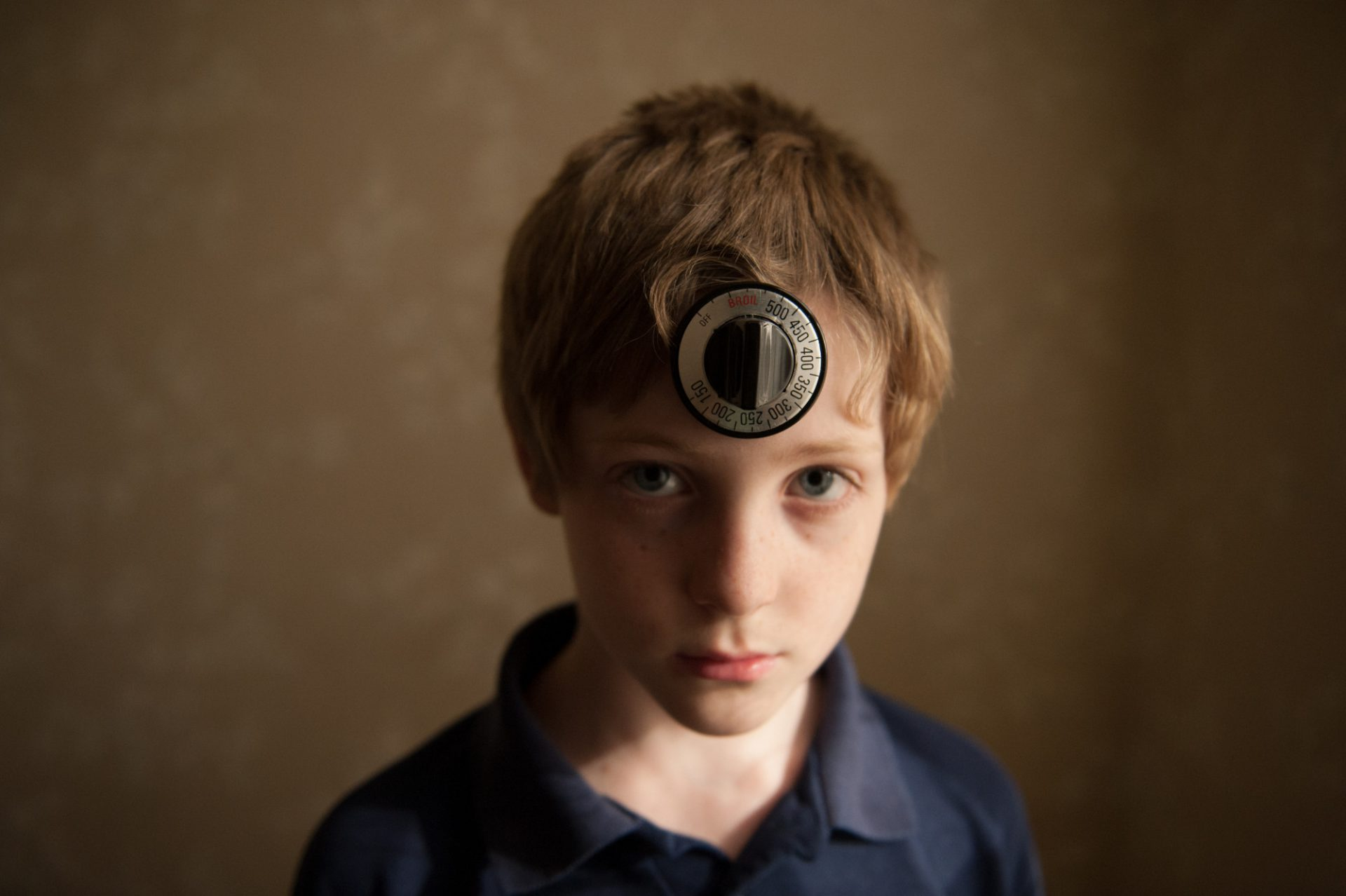 Photo: A portrait of a young boy with an oven knob on his forehead, Lincoln, Nebraska.