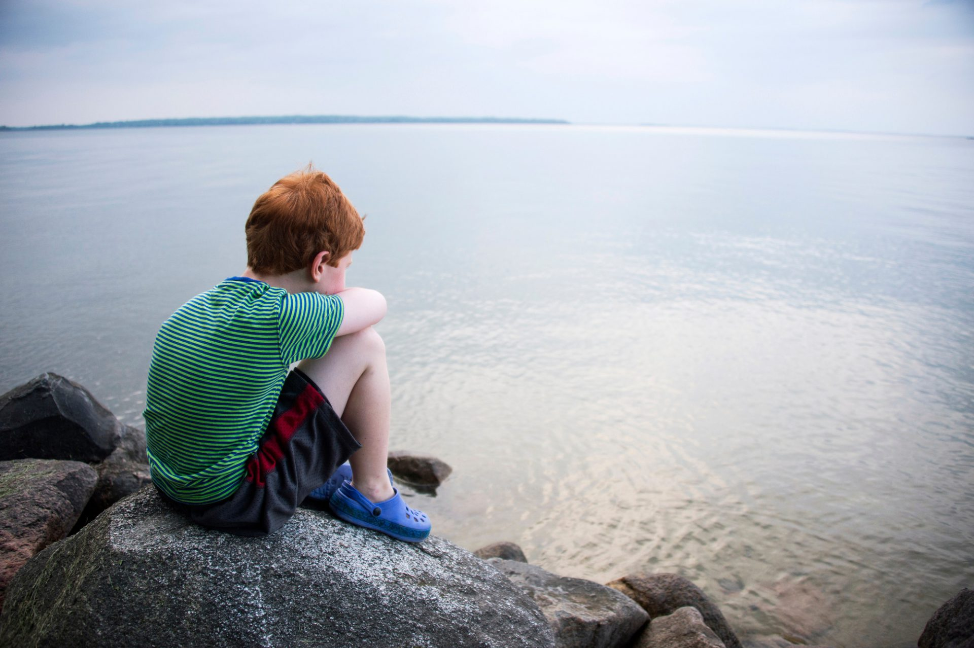 Photo: A young boy stares out over the water at Leech Lake, Minnesota.