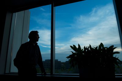 Photo: A man looks out an office window.
