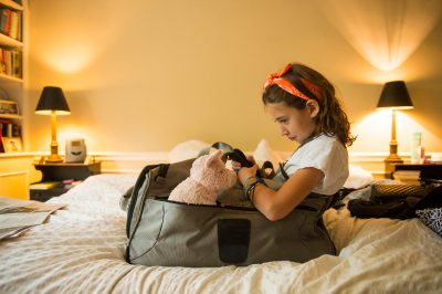 Photo: An elementary age girl pouts while sitting in her mother's suitcase.