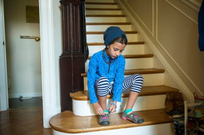 Photo: An elementary age girl puts on her shoes on the stairway of her home.