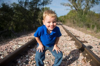 Photo: An elementary aged boy poses for a portrait on railroad tracks.