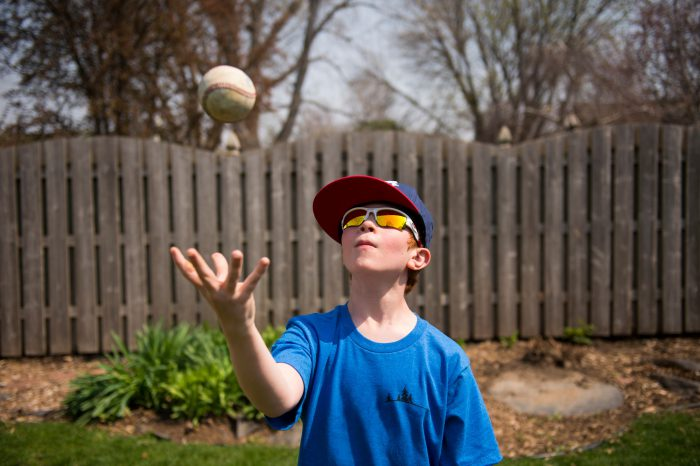 Photo: An elementary age boy throws a baseball into the air.