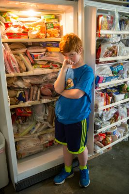 Photo: An elementary age boy stands in front of his grandmother's very stuffed freezer.