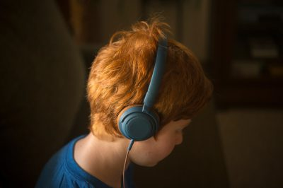 Photo: An elementary age boy listens to headphones.