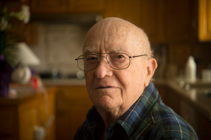 Photo: A portrait of an elderly man in his kitchen.